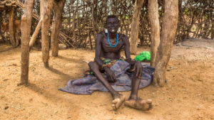 43485573 - omo valley, ethiopia - may 6, 2015 : old warrior from the african tribe daasanach relaxing in his village.